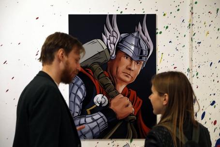epa04965880 Journalists speak in front of a comic book-style artwork depicting Russian President Vladimir Putin as Thor, the Norse mythology's hammer-wielding god of thunder and storms, during the 'Putin Universe' exhibition in Moscow, Russia, 06 October 2015. Moscow and London on 06-07 October host a 'Putin Universe' exhibition organized by international group of Putin's supporters and dedicated to the Russian president's 63rd birthday. The exhibition presents Russian President Vladimir Putin as characters and heroes from various countries and eras. EPA/MAXIM SHIPENKOV