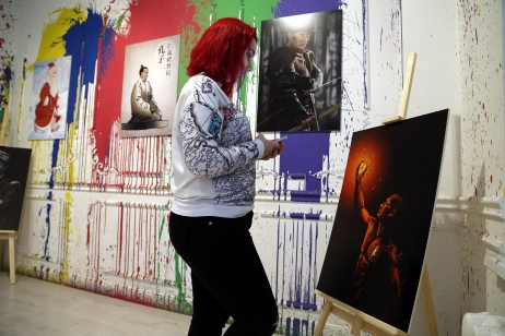 epa04965881 A journalist looks at an artwork depicting Russian President Vladimir Putin as Russia's writer Maxim Gorky's character, Danko, holding his flaming heart, during the 'Putin Universe' exhibition in Moscow, Russia, 06 October 2015. Moscow and London on 06-07 October host a 'Putin Universe' exhibition organized by international group of Putin's supporters and dedicated to the Russian president's 63rd birthday. The exhibition presents Russian President Vladimir Putin as characters and heroes from various countries and eras. EPA/MAXIM SHIPENKOV