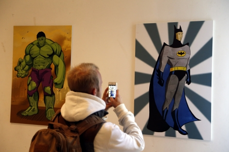 epa04965882 A journalist takes picture with his mobile phone of artworks depicting Russian President Vladimir Putin as comicbook characters 'The Incredible Hulk' (L) and as Gotham City super-hero protector 'Batman' (R) during the 'Putin Universe' exhibition in Moscow, Russia, 06 October 2015. Moscow and London on 06-07 October host a 'Putin Universe' exhibition organized by international group of Putin's supporters and dedicated to the Russian president's 63rd birthday. The exhibition presents Russian President Vladimir Putin as characters and heroes from various countries and eras. EPA/MAXIM SHIPENKOV