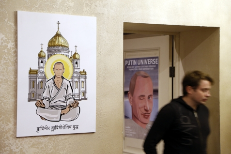 epa04965884 A journalist arrives to the 'Putin Universe' exhibition as he passes an artwork depicting Russian President Vladimir Putin as Buddha (L) in Moscow, Russia, 06 October 2015. Moscow and London on 06-07 October host a 'Putin Universe' exhibition organized by international group of Putin's supporters and dedicated to the Russian president's 63rd birthday. The exhibition presents Russian President Vladimir Putin as characters and heroes from various countries and eras. EPA/MAXIM SHIPENKOV