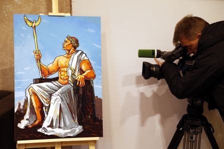 epa04965885 A cameraman stands near an artwork depicting Russian President Vladimir Putin as the ancient Roman mythology's god Jupiter of sky and thunder during the 'Putin Universe' exhibition in Moscow, Russia, 06 October 2015. Moscow and London on 06-07 October host a 'Putin Universe' exhibition organized by international group of Putin's supporters and dedicated to the Russian president's 63rd birthday. The exhibition presents Russian President Vladimir Putin as characters and heroes from various countries and eras. EPA/MAXIM SHIPENKOV