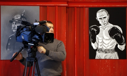 epa04965888 A cameraman stands in front of artworks depicting Russian President Vladimir Putin as prominent Prussian statesman Otto von Bismarck (L) and a famous heavyweight boxer Muhammad Ali (R) during the 'Putin Universe' exhibition in Moscow, Russia, 06 October 2015. Moscow and London on 06-07 October host a 'Putin Universe' exhibition organized by international group of Putin's supporters and dedicated to the Russian president's 63rd birthday. The exhibition presents Russian President Vladimir Putin as characters and heroes from various countries and eras. EPA/MAXIM SHIPENKOV